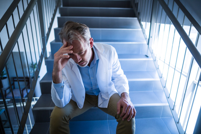 Sad doctor sitting on staircase in hospital